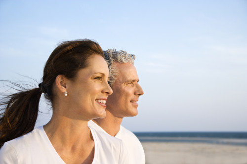 Side view of smiling middle aged couple on beach looking off int